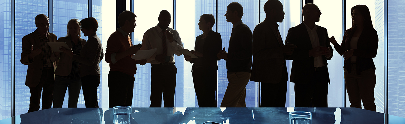 Professionals standing and talking in a conference room