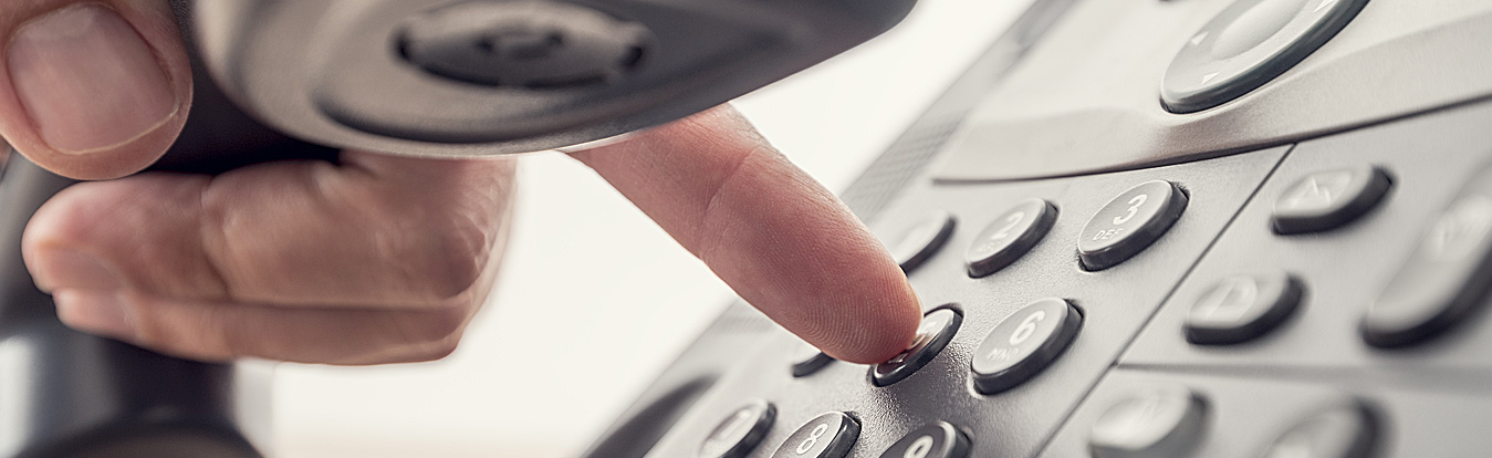 Photo of a person's hand holding a phone and dialing a phone number.