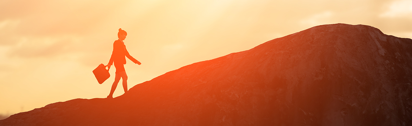 Image of a woman walking up a mountain