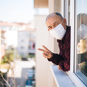 Man wearing surgical mask leaning out his window