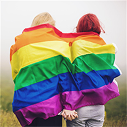 A couple draped in a rainbow flag